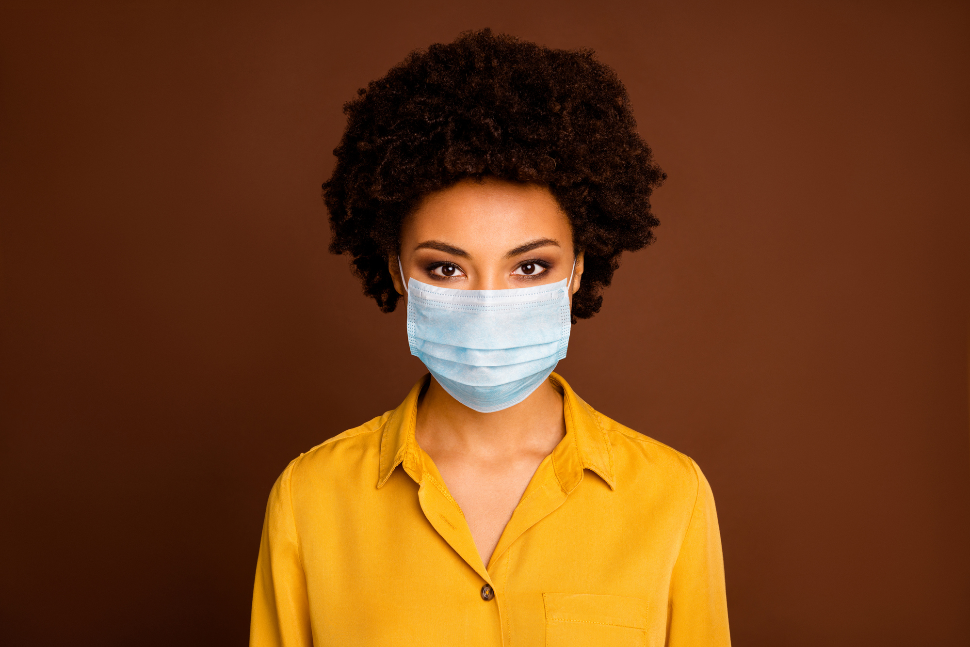 Close-up portrait of pretty dark skin wavy-haired lady in yellow shirt gauze mask concept sickness illness disease life sars cov ncov prevention isolated