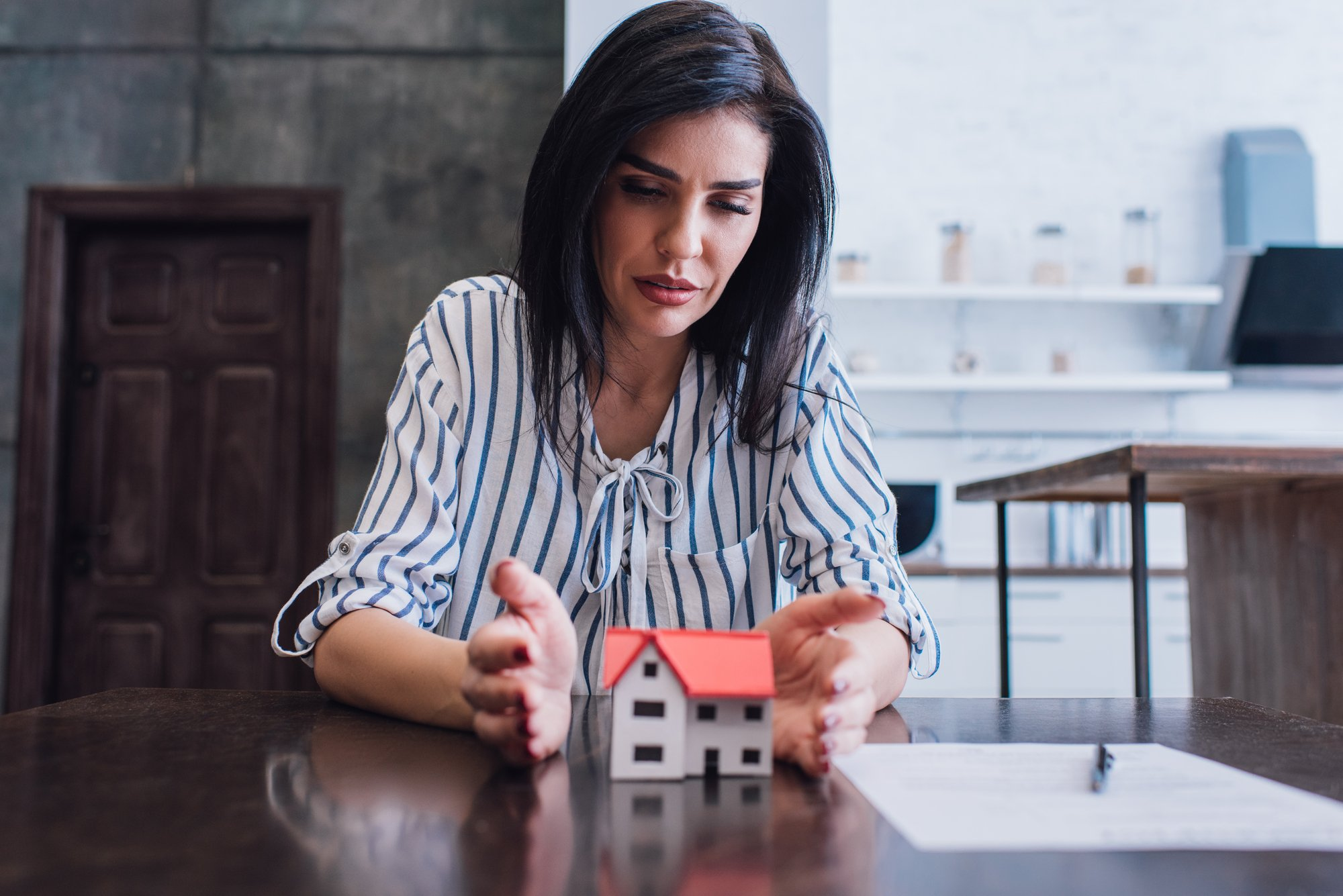Concentrated woman putting hands near house model with paper and pen on table in room