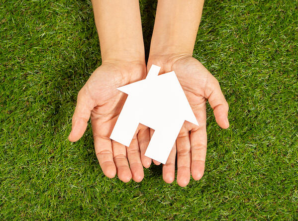 Conceptual picture of woman hands holding white house over green grass field top view and copy space in Property investment Real estate Saving and buying a home mortgage and loan bank
