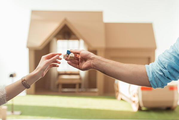 Cropped shot of real estate agent passing key to client in front of cardboard house