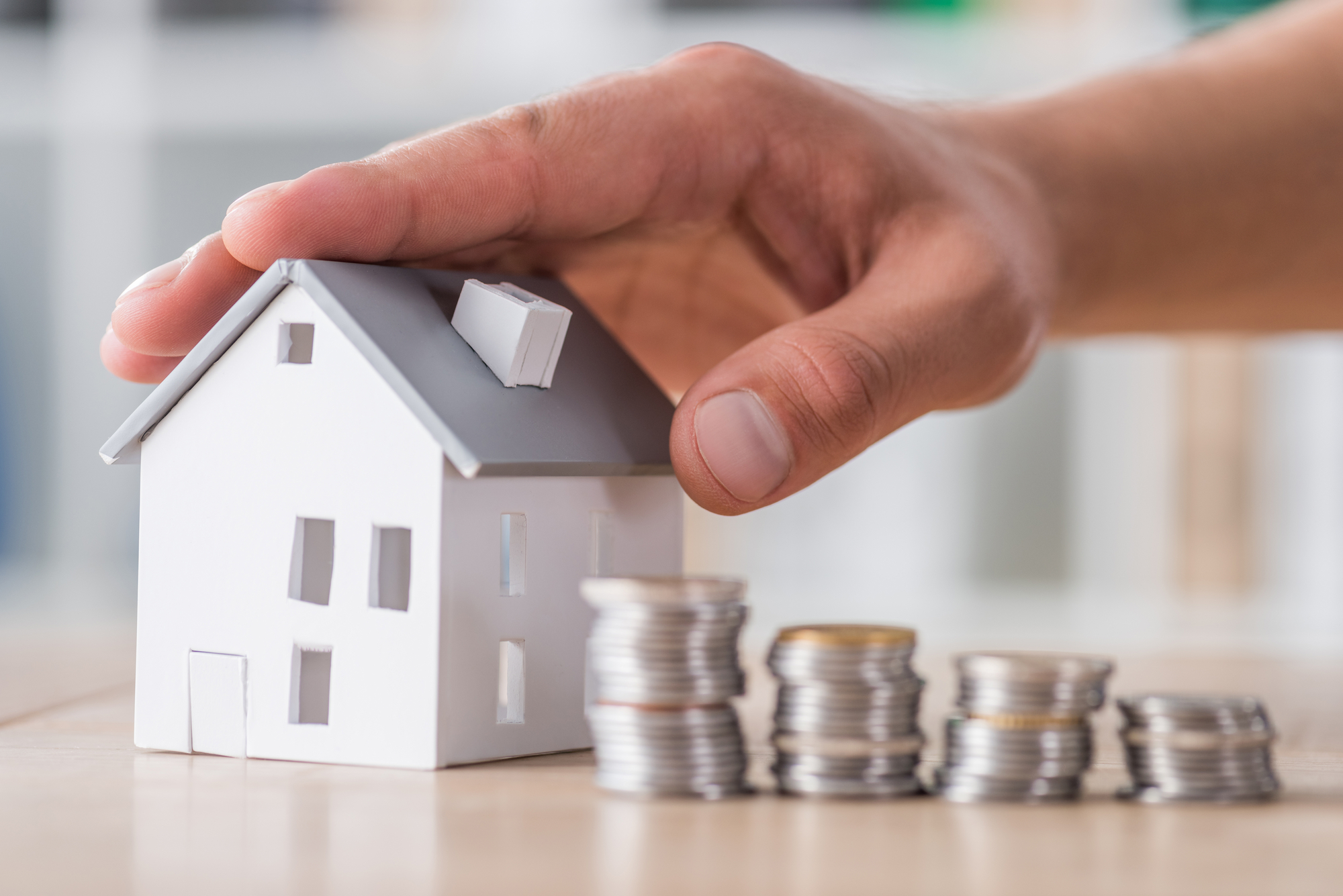 Cropped view of businessman touching roof of house model near stacked coins