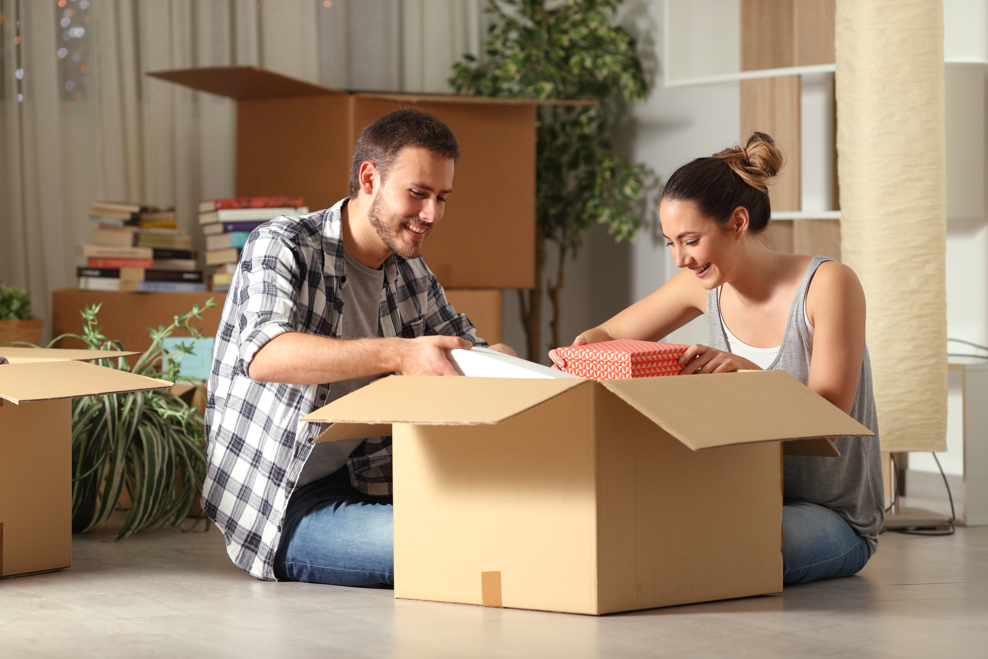 Happy couple unboxing belongings moving house on the floor
