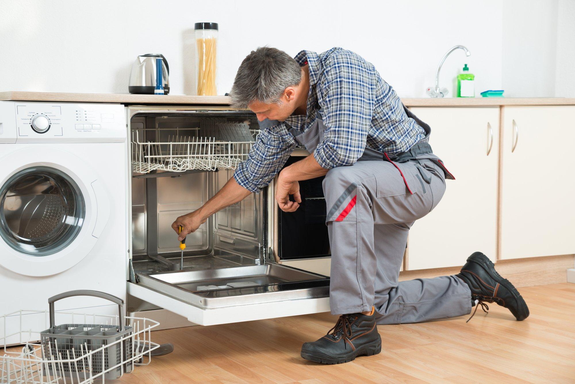 Repairman Repairing Dishwasher With Screwdriver In Kitchen