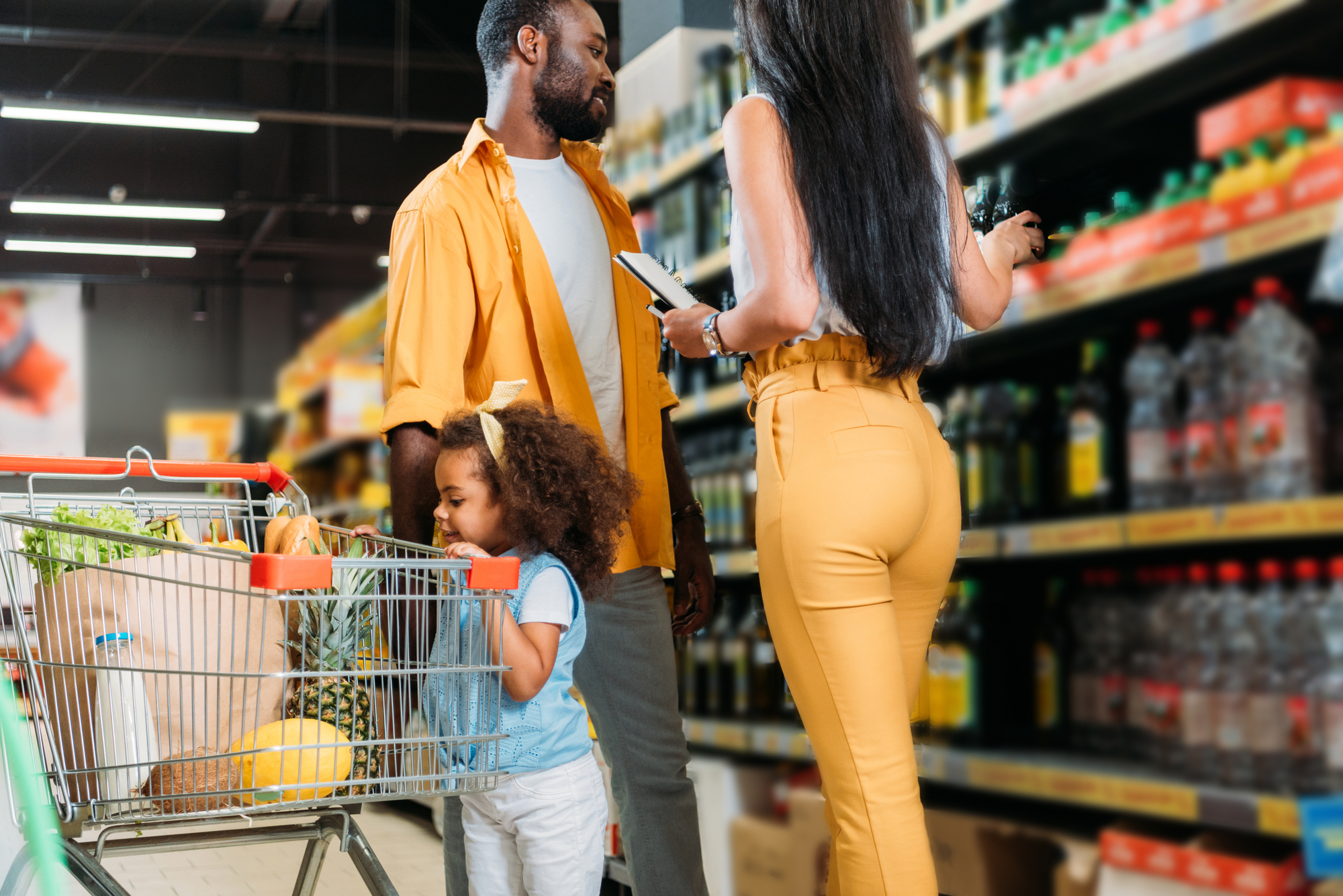 Selective focus of african american couple choosing food while their daughter standing with shopping trolley in hypermarket