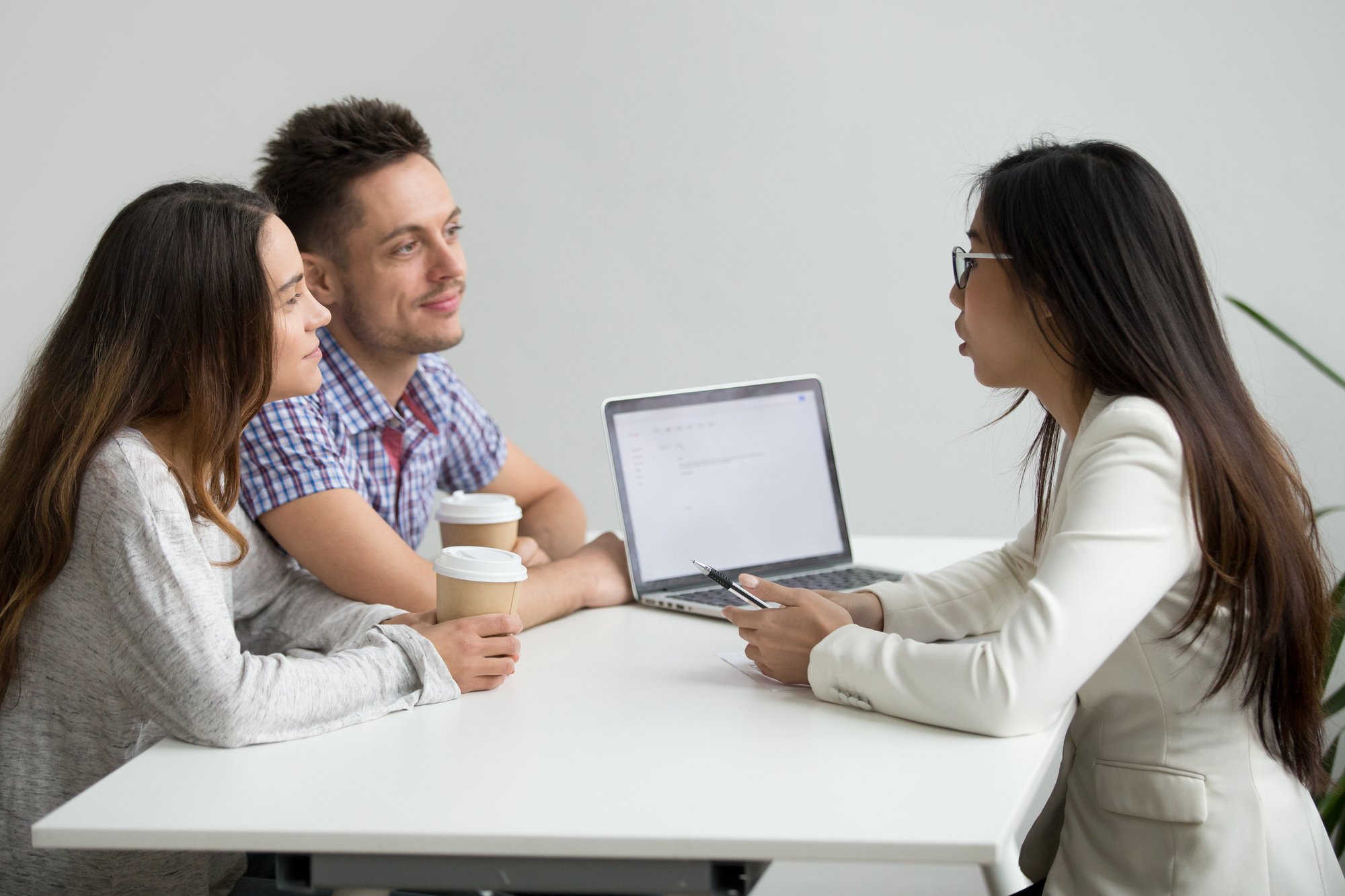 Smiling millennial couple listening to asian advisor lawyer cons