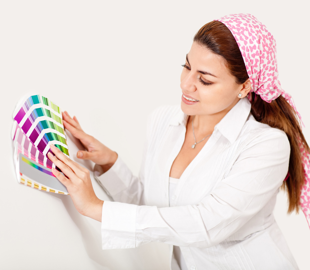 Woman painting the wall and holding a color guide