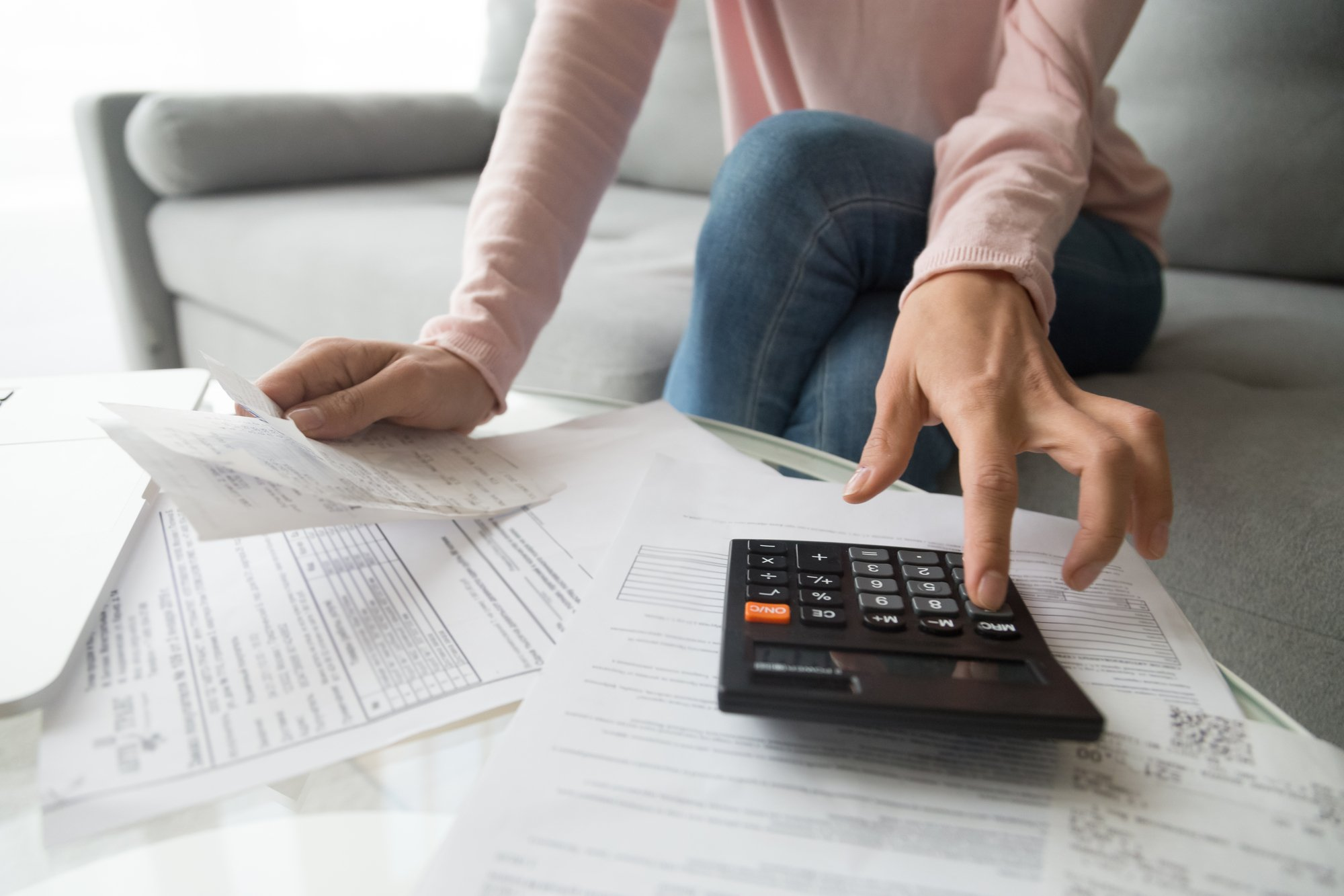 Woman holding bills using calculator manage finances, close up view