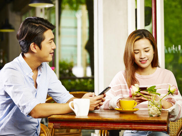 Young asian man and woman sitting at table chatting talking playing with cellphone in coffee shop or tea house